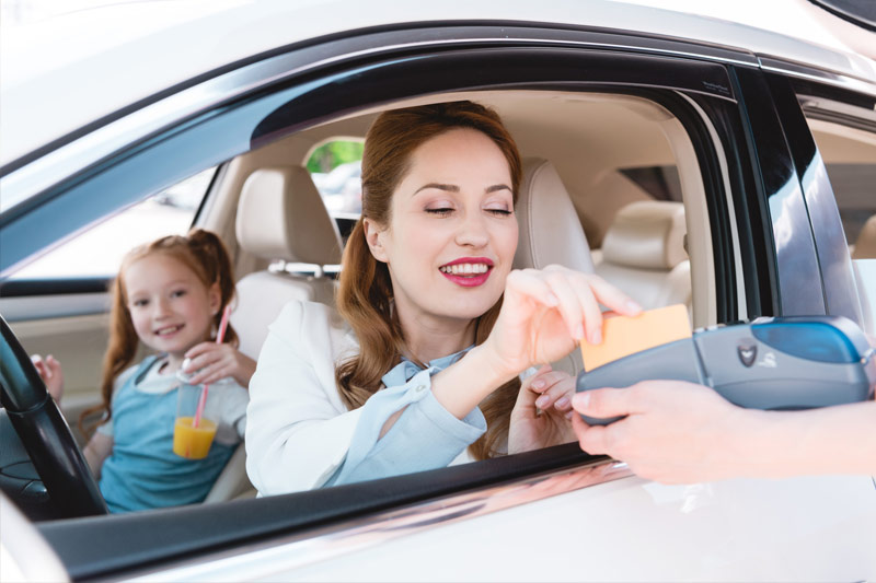 Photo of mom in her car with child paying for a gift card curbeside.