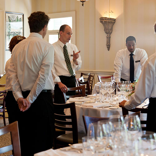 A group of servers meeting in the dining room before dinner service