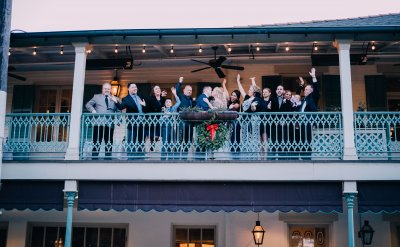 Family celebrating with Bride & Groom on balcony